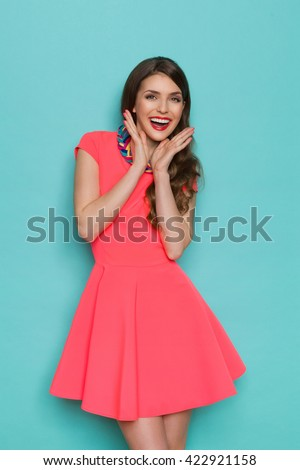 Excited beautiful young woman in pink mini dress posing with hands on chin. Three quarter length studio shot on turquoise background. - stock photo