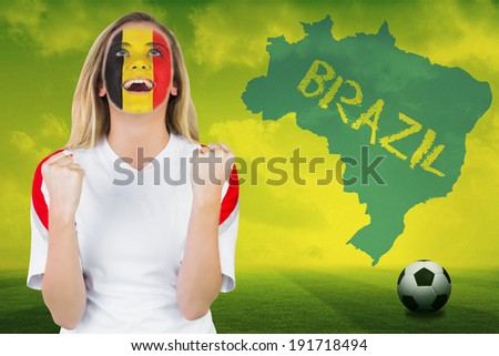 Excited belgium fan in face paint cheering against football pitch with brazil outline and text - stock photo