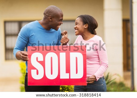 excited black couple holding sold sign outside their house - stock photo