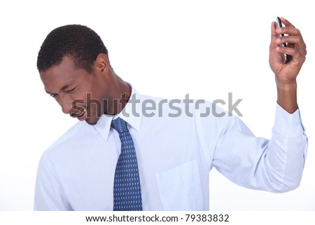 excited black man wincing and holding a cell phone in his hand - stock photo