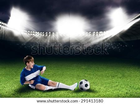 Excited boy football player at stadium kicking ball - stock photo