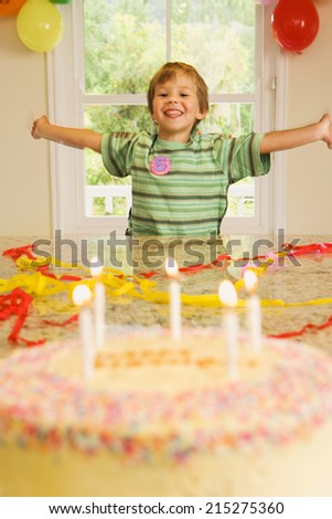 Excited boy (4-6) sitting at end of table at home, arms out, looking at birthday cake in foreground, smiling, front view, portrait - stock photo