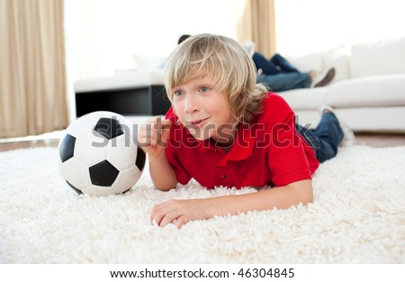 Excited boy watching football match lying on the floor in the living-room - stock photo