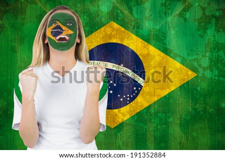 Excited brasil fan in face paint cheering against brazil flag in grunge effect - stock photo