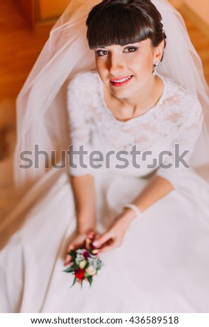 Excited bride in gorgeous white dress waiting for her wedding posing with cute floral boutonniere - stock photo