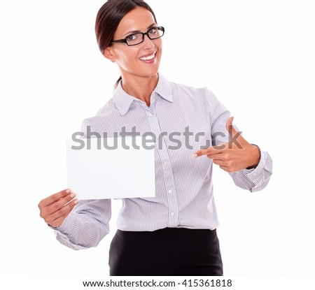 Excited brunette businesswoman with glasses, wearing her long hair tied back, and a button down shirt, holding a blank signboard in one hand, and pointing at it with the other hand