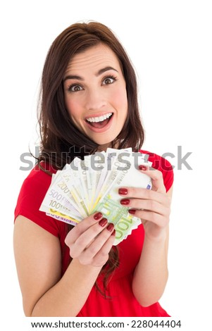 Excited brunette holding her cash on white background