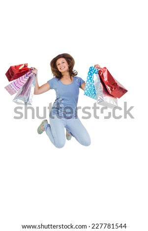 Excited brunette jumping while holding shopping bags on white background - stock photo