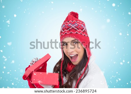 Excited brunette opening a christmas gift against blue vignette - stock photo