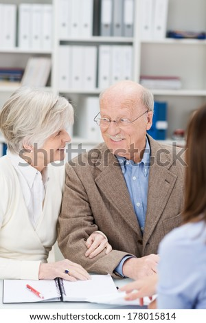 Excited business couple in a meeting with a broker or financial adviser looking at each other as they consider her proposal - stock photo