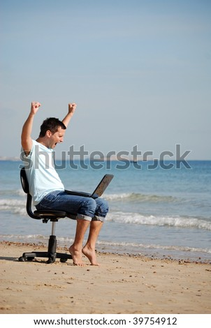 Excited business man cheering on beach