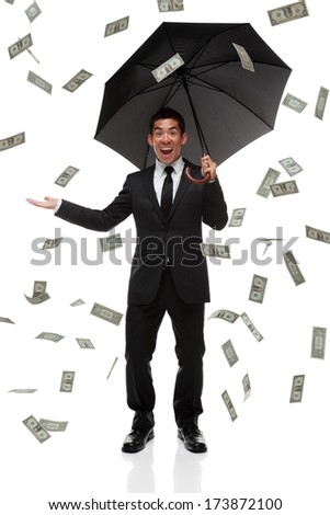 Excited business man looking at camera in a money rain storm - stock photo