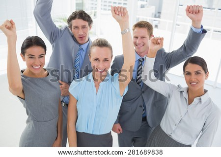 Excited business team cheering at camera in the office - stock photo