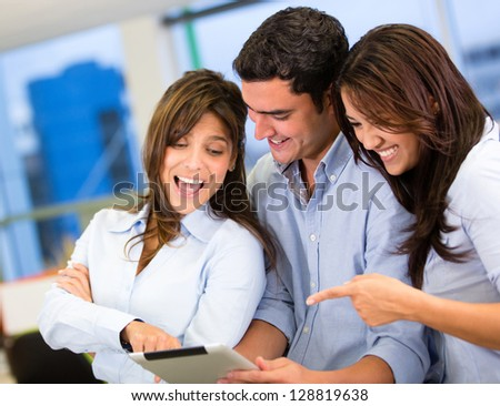 Excited business team with a tablet computer at the office - stock photo