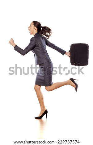 Excited business woman running and holding a briefcase - stock photo