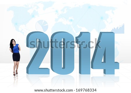 Excited business woman standing next to a 2014 with world map background