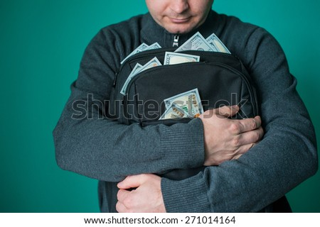 excited businessman holding black bag with money. - stock photo