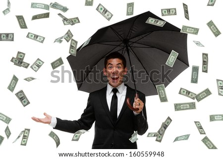 Excited businessman looking at camera in a money rain storm - stock photo