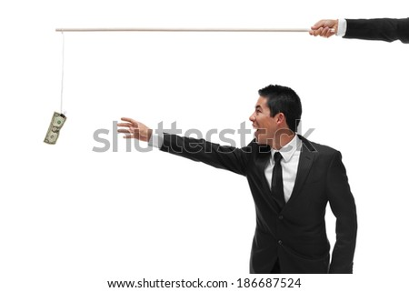 Excited businessman reaching for money on the end of a stick being bribed half body - stock photo