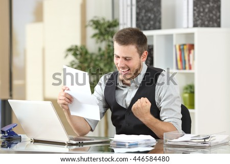 Excited businessman reading good news in a a letter in a desktop at office - stock photo