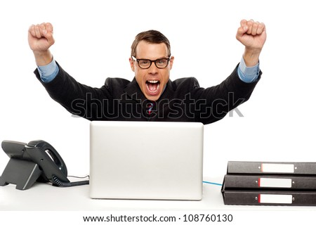 Excited businessman shouting and rejoicing his victory. Wearing glasses and arms raised up - stock photo