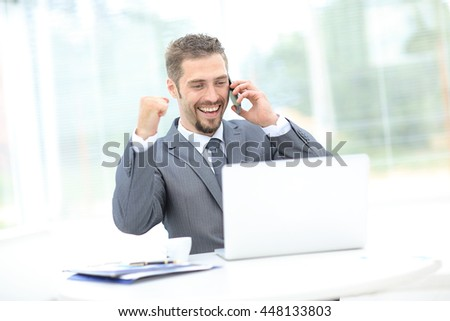 Excited businessman talking on the mobile phone while is watching business content in a laptop