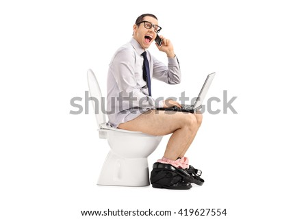 Excited businessman working on laptop and talking on phone seated on a toilet isolated on white background - stock photo