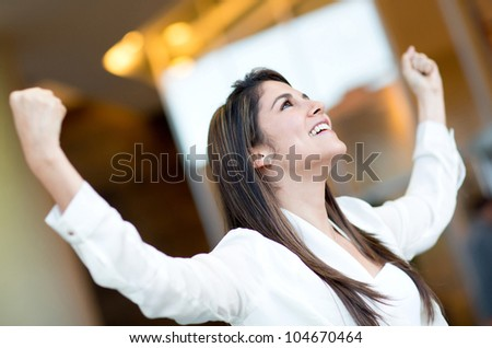 Excited businesswoman celebrating her triumph with arms up - stock photo