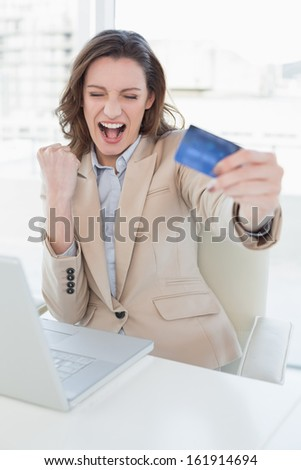 Excited businesswoman doing online shopping through laptop and credit card in office