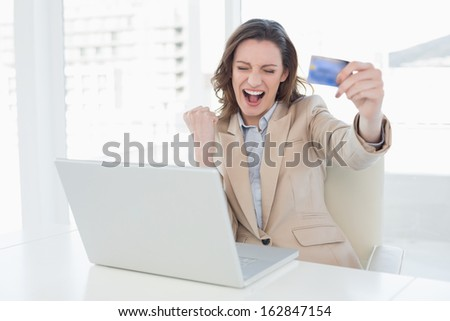 Excited businesswoman doing online shopping through laptop and credit card in office - stock photo