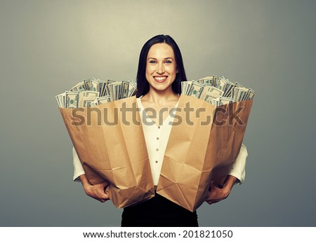 excited businesswoman holding paper bag with money and smiling. photo in studio over grey background - stock photo