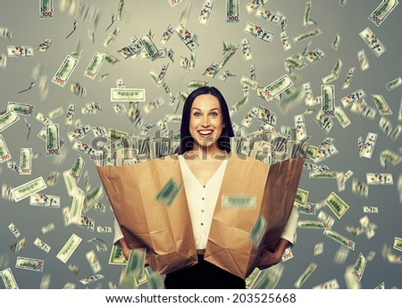 excited businesswoman standing under dollar's rain, holding big paper bag with money and looking at camera - stock photo
