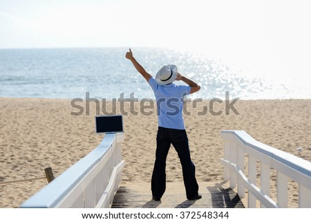 Excited busy male working on the laptop and talking on mobile. Man in hat speaking on smartphone over blue sky and ocean background - stock photo
