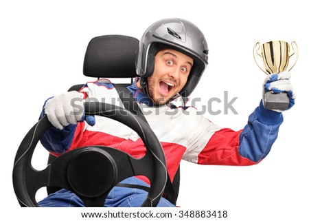 Excited car racer holding a gold trophy seated on a car seat and looking at the camera isolated on white background - stock photo