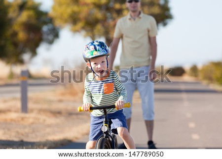excited caucasian boy riding a balance bike and his father waiting - stock photo