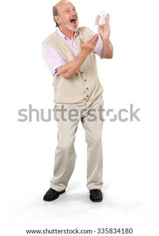 Excited Caucasian elderly man with short grey hair in casual outfit holding playing cards - Isolated - stock photo