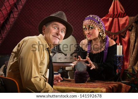 Excited Caucasian man with grinning crystal ball reading lady
