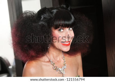 Excited Caucasian woman with afro haircut and big grin - stock photo