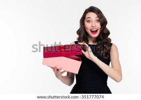 Excited cheerful attractive young woman with retro hairstyle in black dress opening gift over white background - stock photo