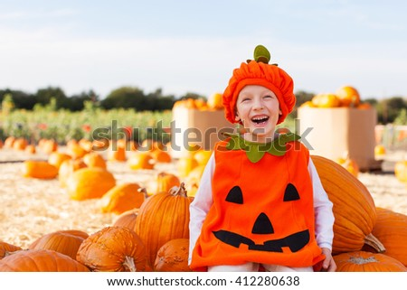 excited cheerful boy in pumpkin costume enjoying pumpkin patch and autumn time ready for halloween - stock photo