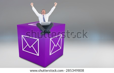 Excited cheering businessman sitting using his laptop against grey vignette - stock photo