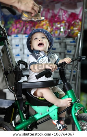 Excited child on a tricycle in shop