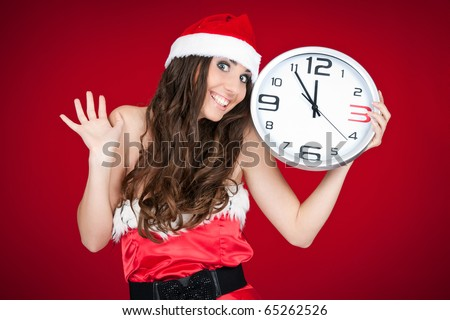 excited Christmas girl holding clock and pointing at time - stock photo
