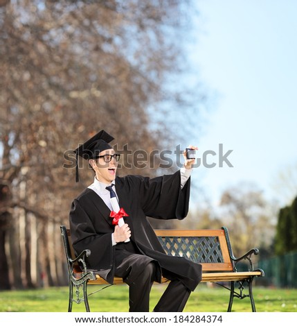 Excited college graduate taking a selfie on a bench in park shot with tilt and shift lens - stock photo
