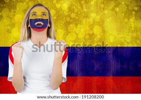 Excited colombia fan in face paint cheering against colombia flag in grunge effect - stock photo