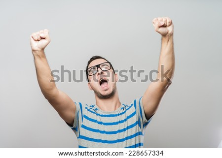 Excited corporate guy clenching his fists - stock photo