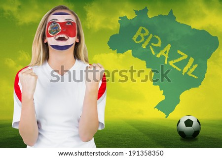 Excited costa rica fan in face paint cheering against football pitch with brazil outline and text - stock photo