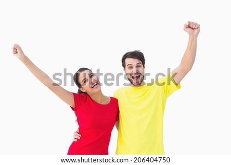 Excited couple cheering in red and yellow tshirts on white background - stock photo