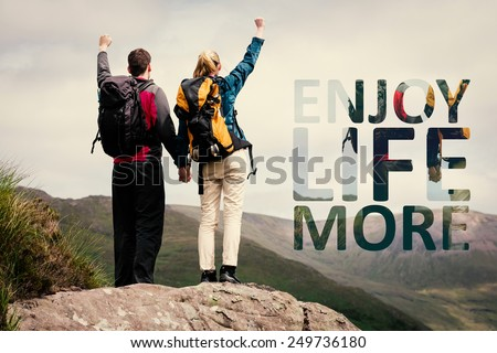 Excited couple reaching the top of their hike and cheering against enjoy life more - stock photo