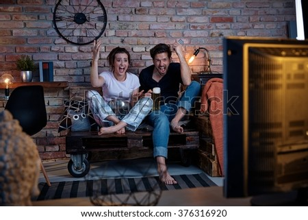 Excited couple watching tv at home, jittering. - stock photo